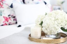 Guest bedroom with white bedding, gold decor, floral pillows and tassels