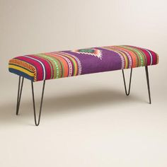 Our hairpin leg bench inspires a boho vibe with its cushioned seat covered with handwoven rug-like fabric in a Southwest print. This charming seat is a colorful addition to the entryway, living room or bedroom.