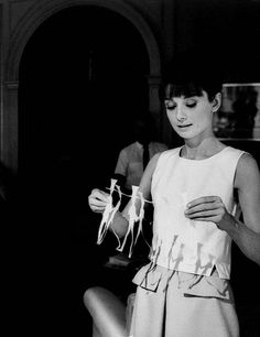 Audrey Hepburn proudly looks at the chain of paper doll silhouettes she's just just made (http://tmblr.co/ZvUb-x1T-I_VI). She was on a break between shoots on the set of Paris, When It Sizzles in 1963.