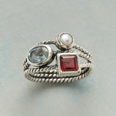 ROPED REUNION RING -- Roped sterling silver separates and gathers a trio of semi-precious stones—pearl, garnet and blue topaz. Exclusive. Whole sizes 5 to 10.