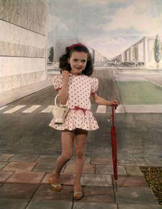 Kindermode, atelierfotografie. Meisje poseert met metalen emmertje en paraplu, in zomerjurkje met verlaagde taille en pofmouwtjes, van stippenstof, op houten slippers (kleppertjes). Studio-opname in een stedelijk-decor, met stoeptegels en een door de fotograaf geschilderde achterwand met straten en gebouwen. Nederland, 1962.