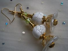 Ohrringe mit goldenen Schmuckelementen, die sich vorsichtig auf den zarten üppingen Blüten in weiß niedergelassen haben.   Transparenz in mattem weiß