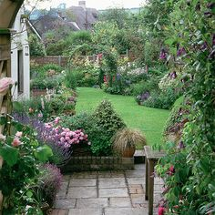 Classic country garden lawn Colourful plants and flowers are a must in a country-style garden. Here, the front paved courtyard is edged in roses, lavender and clematis, and leads down to the lawn and borders planted with hardy geraniums, verbascum, and campanula.