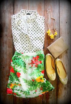 Polka dot blouse, floral skirt, yellow statement necklace with gold flats and clutch