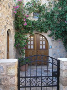 Residence in a medieval seaside town. This doorway is located in Monemvasia, Greece. I love an iron gate, especially with a courtyard. House Front Gate, Front Gates, Entrance Doors, Doorway, Monemvasia Greece, Fence Gate, Fences, Greek House, Brown Doors