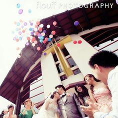 Great shot by FLOUFF Photography. A kiss on a forehead along with the release of colorful balloons into the air after their Holy Matrimony.