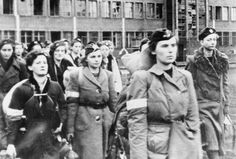 Female Polish fighter of the Warsaw Uprising, 1944, march into German captivity after the uprising was crushed by the Waffen SS. Most of these defiant women perished in death camps, their status as low as that of Soviet POWs.