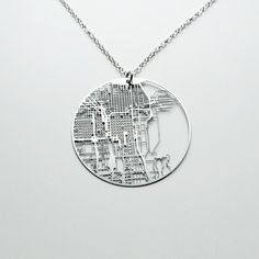 There is more than meets the eye to thismesmerizing necklace.The intricately detailed circle pendant containsa delicate grid map of an iconic urban center.Show your city savvy by honoring this influential cultural hub around your neck. Available in maps of Beverly Hills, Chicago, and San Francisco.