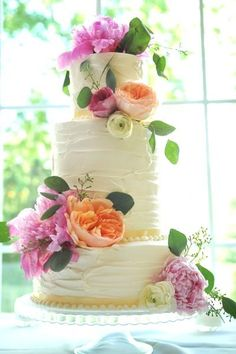 double height tier, soft iced wedding cake finished with pretty peonies. Visit www.rosetintmywedding.co.uk for bespoke planning and design