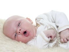 A baby lying on her side and making an 'o' shape with her mouth.