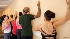 Stand facing a wall and brace yourself with your left fingertips at shoulder level. Place your right elbow and forearm against the wall slightly higher than shoulder height. Take a breath in and lift your armpits and rib cage up toward your ears so the sides of your body get long. As you pull your shoulder heads, head and neck back, curl the upper thoracic spine in and up. Keep your chin open. Maintaining this alignment, exhale and turn your feet to the left, increasing the stretch to the…