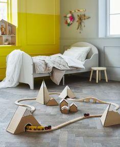 In einem Kinderzimmer ist eine Spielzeugeisenbahn zu sehen, die durch einen mit Karton gebastelten Tunnel fährt.