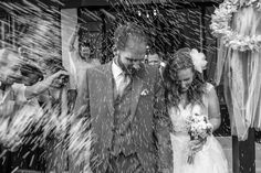 Bride and groom exiting church while relatives and friends throw rise at them