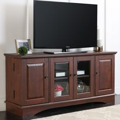 "52"" Media Storage Wood TV Stand/Console in Medium Traditional Brown Finish. Accommodates most flat-panel TVs up to 55 in. High-grade MDF and durable laminate construction. Double doors with glass panes. Holds approximately 150 DVDs/Blu-ray discs. Item ships within 1 business day! Any order that is received before 12:00 noon MST will ship out same business day!!."
