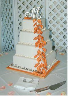 "Mango colored mini sugar callas on this off set fondant cake. Gum paste ""M"" on top."