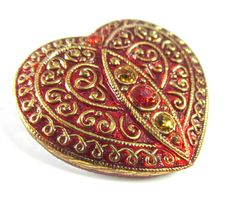 An absolutely gorgeous dark red glass button with a delicate gold pattern embossed on the front. Three crystal chatons enhance the center of the hear (1 red and 2 smaller gold). Finished with a silver