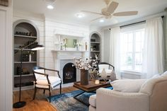 I wanted to really highlight that feeling in the living room by using classic details like shiplap walls, these arched-frame built-in bookcases, and an antique fireplace surround.