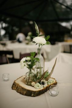 White floral centerpiece on wood round  | Erin & Geoffrey Photography