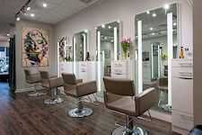Backlit Wall Mount Custom Styling Stations with glimpse of Matching Double Sided Station in Mirror Side Mounted Custom Pedistal Styling Station Cabinets and Bossa Nova Hydraulic Styling Chairs all designed and manufactured by Salon Interiors for Vicki Popp Salon