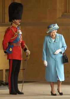 The Queen laughing as she passes her husband, the Duke of Edinburgh in uniform. I love this!