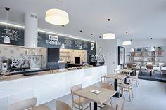 """Srdcem podniku je """"barový"""" prodejní pult s povinnou černou tabulovou barvou na zdi a otevřená kuchyně, ve které je možné sledovat přípravu jídel a nápojů."""