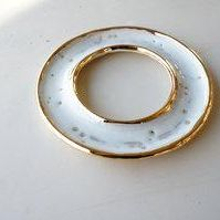 Built by hand and finished in a glossy cream colored glaze with 22k gold luster accents around the rim of both edges.