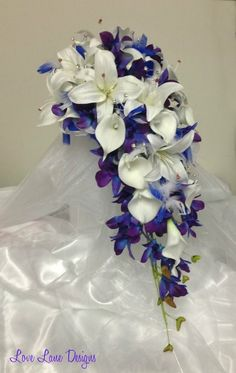 Wispy tufts of royal blue and white feathers with white casablanca lillies, calla lillies and blue singapore orchids, diamante stems, bridal teardrop bouquet