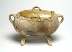 Surrey/Hampshire border whiteware with yellow-glaze. This handled casserole has an oval elongated body on four splayed feet, a handle at each end of the body and one on the lid. The lid and the interior are glazed