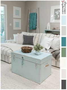 florida living room with mint blue accents, warm gray walls, teal green throw, charcoal gray throws, cream striped sofa, mint blue painted trunk, trunk coffee table, light sand carpet, white accents, driftwood decor, driftwood decorative ladder, pale blue, light blue, sky blue, baby blue, sherwin williams icelandic