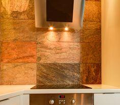 Okap naścienny w aranżacji nowoczesnej kuchni. Stalowy kolor okapu doskonale komponuje się ze ścianą wykonaną z łupków.