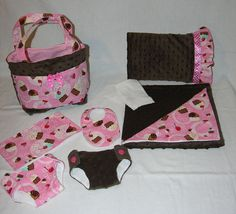 The Baby Basics Collection has everything your littlest Mommy needs for her baby doll. With the absolute Mommy must-haves of diapers, wipes and a diaper bag to carry it all in.  Love the material used sweet cupcake print with cherries on pink, coordinating brown minky and lined with white flannel