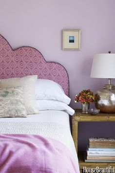 The daughter's bedroom is painted in Benjamin Moore's Misty Lilac. The headboard is in Raoul Textiles' Coverlet, and the Bungalow side table is by Serena & Lily.   - HouseBeautiful.com