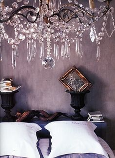 Love the dusky walls, the crisp pillows, the chandelier, and most of all the tiny framed picture set askew inside the urn.