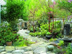 A beautifully laid stone path, combined with stone containers and salvaged architectural details in a garden designed by Phil Wood; Jim DuBois was the stonemason.