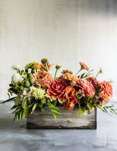 A box we'd be happy to think inside of: Dahlias, zinnias, unripe blackberries, alstroemeria, and assorted greenery all displayed in an unusual wooden box.