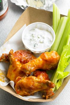 It would hardly be game day without a sticky pile of chicken wings and cool blue cheese dipping sauce. These zesty Buffalo chicken wings get their spicy orange exterior from a double dose of hot sauce. #superbowlrecipes #appetizers #tailgaterecipes #fingerfoods #apps #bhg Healthy Superbowl Snacks, Game Day Snacks, Game Day Food, Appetizer Recipes, Snack Recipes, Cooking Recipes, Holiday Appetizers, Party Appetizers, Party Recipes