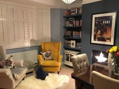 Yellow IKEA Strandmon chair against Little Greene Juniper Ash and Pale Wedgewood paint. Cosy reading corner with a pop of colour. A modern star-shaped light takes the place of a traditional fire.