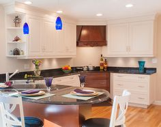 Kitchen Remodel in Tewksbury MA! Two tone kitchen, back granite countertops, blue pendant lights, brown wood carved hood, cherry wood carved hood, corner sink and stove top!