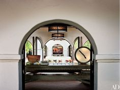 """Monterey furniture served as her inspiration for the table she designed for the office—once an open-air loggia. """"We added doors to the arches and turned it into a year-round room,"""" says Shadley. The painting across the courtyard is a Mell oil   archdigest.com"""