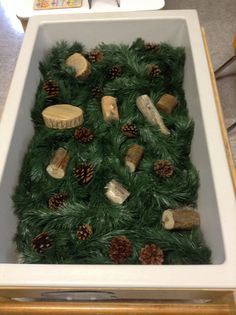 Christmas sensory table! Garland, pine cones, and pieces of wood.