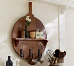 """The classic breadboard is stylishly reinvented as a wall-mounted spice shelf with utensil hooks.  * 24.25"""" wide x 3.5"""" deep x 32"""" high  * Made of mango wood.  * Three iron hooks.  * Catalog / Internet Only."""