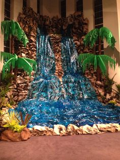 Waterfall made from kraft paper being stapled to cardboard and spray painted. Cellophane and lights for the water. Palm trees made out of carpet rolls and the leaves are cut pool noodles wrapped with table clothes: