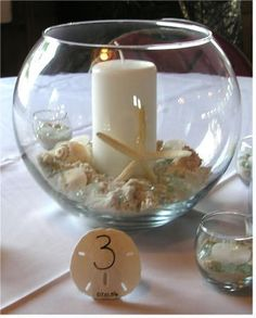 Class bowl center piece with candle and shells for a beach wedding theme and sand dollars for table numbers
