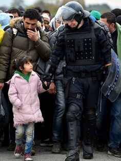 Police escort refugees through Dobova, Slovenia, on their way to a holding camp.  Jeff J Mitchell, Getty Images