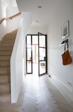 Lichte hal met lichte eiken trap en eiken trapleuning icm een eiken visgraad vloer met witte hoge plint. Woonkamer en hal gescheiden door stalen glazen deur.