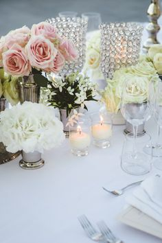 An elegant arrangement of flowers and crystal glasses make great table decorations for the wedding reception #TheTuscanWedding