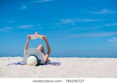 Portrait of a young brunette relaxing on the beach, reading a book