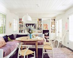 This cozy breakfast nook large bench seating with striped cushions, patterned pillows, colorful rug, rustic wood table and white chairs.