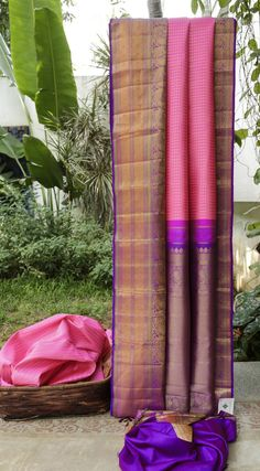 This kanchivaram silk is in fuchsia pink that is checkered with round gold zari bhuttas. The border is in purple with thread work in taffy pink and green along with gold zari work, while the pallu …
