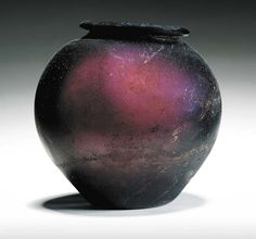 Roman glass bowl, circa 1st-2nd century A.D.  Aubergine in color, free-blown, with a globular body on a slightly convex base, with an everted rounded rim